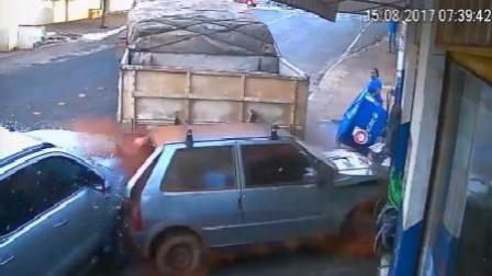 卡车倒车猛踩油门 顶着轿车一起冲进商店