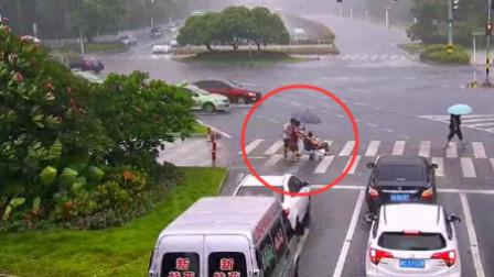 大雨中男子给推轮椅妇女送伞 自己被淋湿