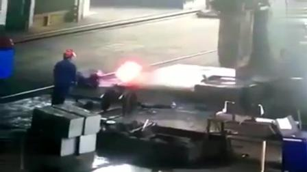 铁匠师傅正在炼钢厂工作, 起锤落锤刚打出铁球形状, 监控下拍到这一幕, 希望师傅安然无事!