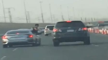 男子探身打司机 不料跌落车外翻滚数圈