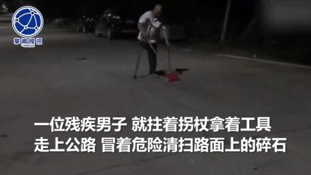 砂石装载车遗落一地碎石 残疾男子拄拐清扫