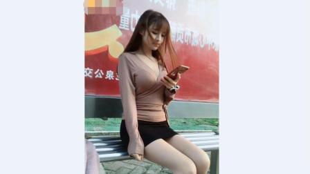 街拍: 身材丰满的小姐姐穿着v领上衣搭配黑色包臀短裙坐那静静的玩着手机好迷人
