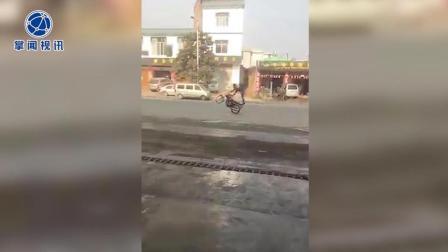 """小青年骑摩托车""""耍杂技"""" 直立行驶引路人心惊"""