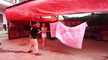 农村媳妇儿晒被子, 老公好心上前帮忙, 却没想到被子里还藏有东西。