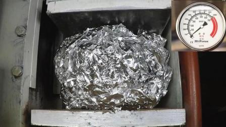 铝箔球放到液压机下, 直接被压成一块铝片, 体积瞬间缩小300倍