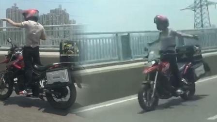 """男子站立在摩托车上 托着外卖箱""""放飞自我"""""""