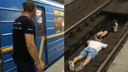 两男子玩冒险趴铁轨中间 让火车从身上驶过