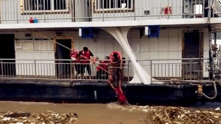 六旬老人洪水中被搭救上船 众人目睹惊险瞬间