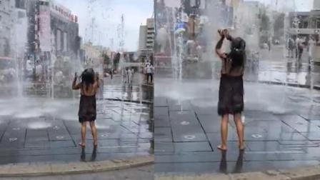 美女穿着清凉当众在喷泉洗澡 还自带洗发水