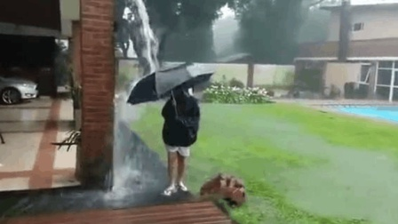 雷雨天外国女孩在屋檐下玩水, 下一秒悲剧了!