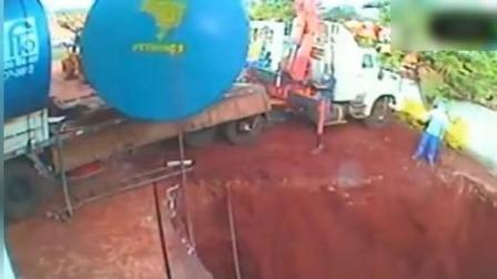 吊车把大油罐吊下坑中, 两男子拉绳子, 下一秒悲剧了