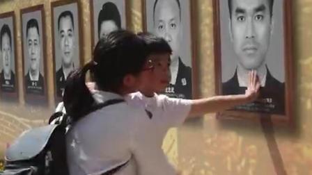 孩子伸出小手摸了摸烈士墙上爸爸的脸