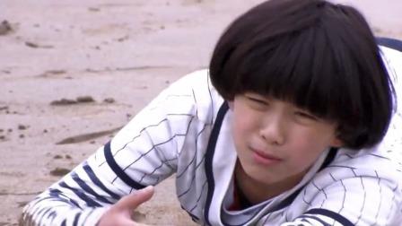 小男孩脚上被绑了沙袋,为了能追上妈妈,直接在沙滩上摔倒了