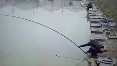 监控实拍: 壮汉钓鱼时被巨物拉入鱼塘, 水中单手擎竿遛鱼上演绝地反击!