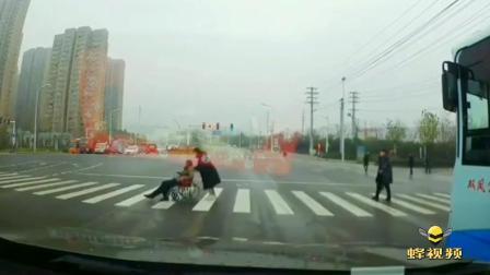 安徽合肥:一轮椅老人过马路红灯亮起 女子上前推行护送