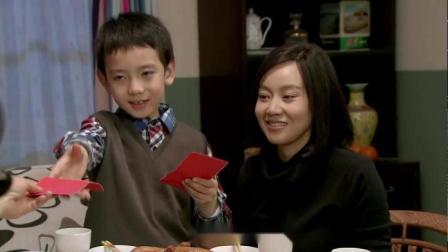 两家人新年团聚,小孩在饭桌上拜年,姥姥奶奶一人给他一个大红包