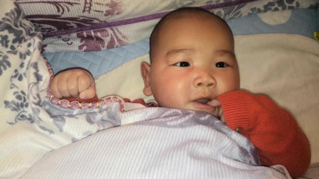 爸爸拿镜头偷偷靠近小宝宝,发现小宝宝正在吃小手,表情萌翻了