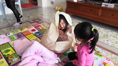 妹妹把姐姐装进大袋子里,提了半天提不动,姐妹俩真是萌翻了
