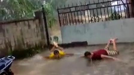 云南久旱后突降暴雨 两男子兴奋得躺地蛙泳