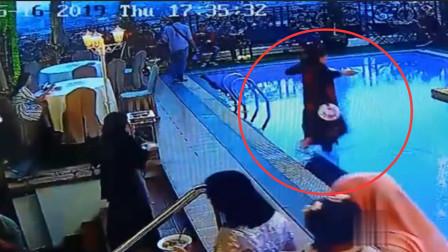女子端餐盘走路不看路 一脚踩空摔进泳池