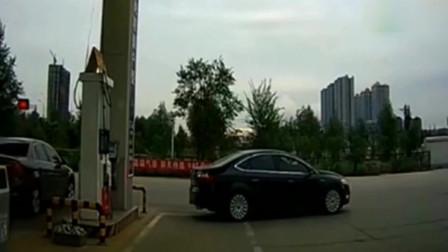 加油员指挥女司机倒车,女司机却不知道怎么打方向盘