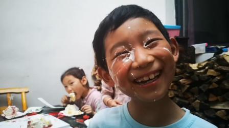 农村小朋友过生日,伙伴一起分享蛋糕,小男生被女生被抹一脸蛋糕