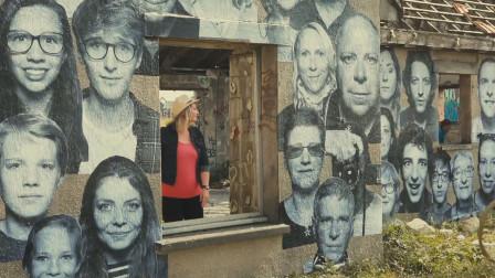 一座废弃的村落,墙上布满了人脸照片,引来各色各样的人参观
