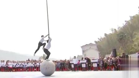 小伙子挑战高空爬杆,更刺激的是脚下竟还踩着球!脚不抖么