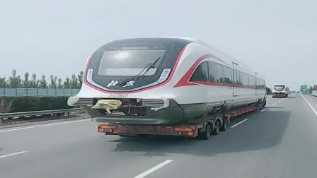 高速路上遇到的一幕,大货车拉着火车头行驶,太霸气了!