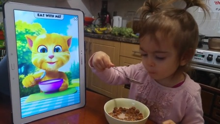 小女孩跟着汤姆猫,一起学吃饭呢,瞧瞧这还有模有样的呢!