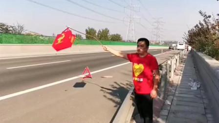 高速爆胎,怕高速上的车看不清路上的三角牌,挥舞红布袋提醒路人