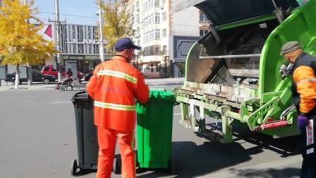 实拍街头垃圾回收作业 环卫工人将分类垃圾箱挂上垃圾回收车