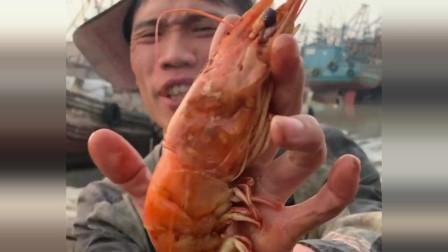 渔民大哥吃一个大的老虎虾,一看就是刚出锅的,简单的吃法也很美味