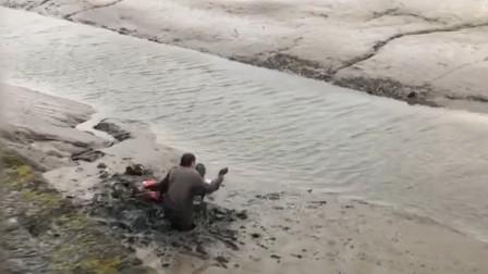 喝醉酒的夫妻为了捡一个酒瓶 竟被困在淤泥之中无法动弹