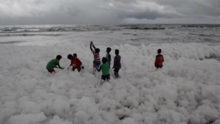 印度海滩布满白色污染物泡沫,孩童却玩得很开心