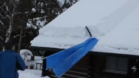 美国阿拉斯加冬季房顶上厚厚的积雪需要用除雪工具清理