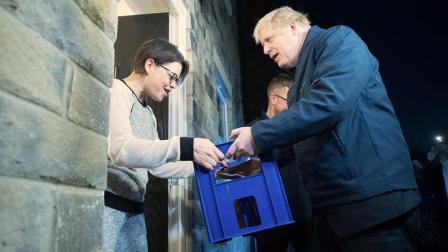 为拉选票拼了!英首相当起搬运工给选民上门送牛奶