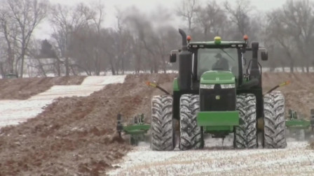 双排车轮就是强劲,重型拖拉机在雪花纷飞中耕地