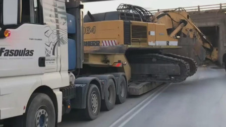 刚好穿越涵洞,重型挖掘机横卧在卡车板车上远程转场