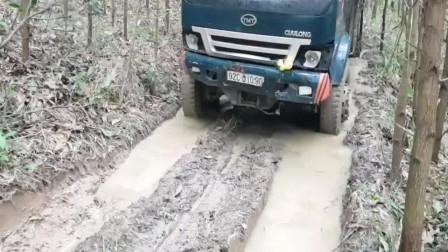 卡车满载木材下坡,这路都是泥浆水