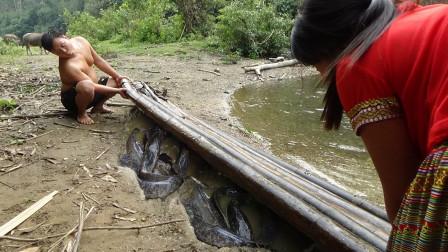 深山妇女,出来采野菜,在河边休息,发现竹排下有鱼,表哥路过帮忙,齐力抓获很多大鱼