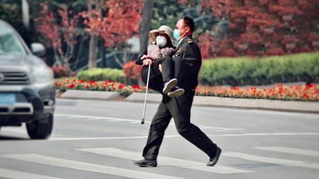 看到拄着拐杖过马路的她,有陌生人主动将她抱起!