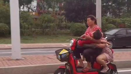 大姐单手骑电动车,一个抱在怀中,一个在后面坐着,孩子都睡着了,太多不安全因素,看着揪心!#阜阳