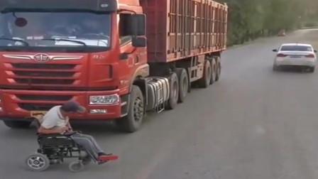 监控实拍:,老头坐轮椅在马路上拦车要过路费,不给钱就不让走!