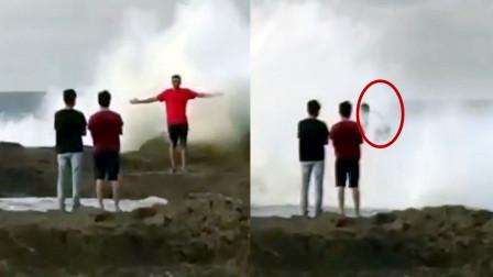 """实拍男子背对大海拍照 下一秒被巨浪""""吞噬"""" 目击者拍下惊险一幕"""