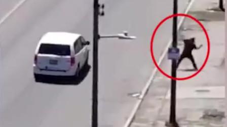 无聊小伙马路上扔石头砸中小车,车主忍无可忍掉头将他怼飞