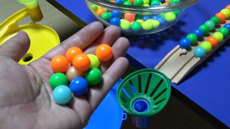 两种彩色弹珠玩具通过木制积木轨道