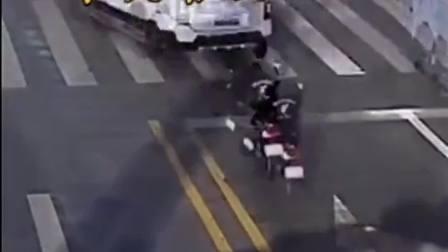 男子骑车马路上酒坛子不慎跌落,留下一地的玻璃碴