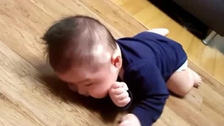宝宝在木地板上努力翻身,最后终于成功了,宝宝高兴的样子太可爱