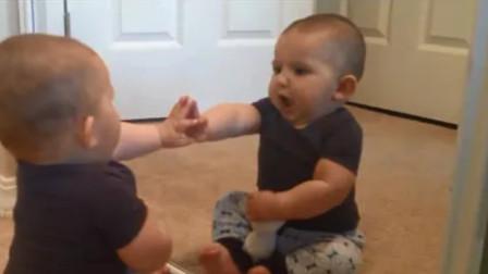 小宝宝正一个人玩着,一抬头发现镜子里竟也有一宝宝,这表情太逗了